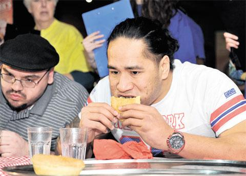 IN PLAY: Newport Gwent Dragons rugby player Andy Tuilagi in a charity pie-eating competition at the Walkabout Bar, below, left, in Cardiff, in aid of the George Thomas Hospice