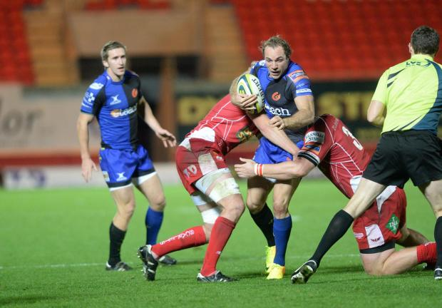 South Wales Argus: Scarlets v Dragons 081113 Will Harries is tackled by two Scarlets players. (2393057)