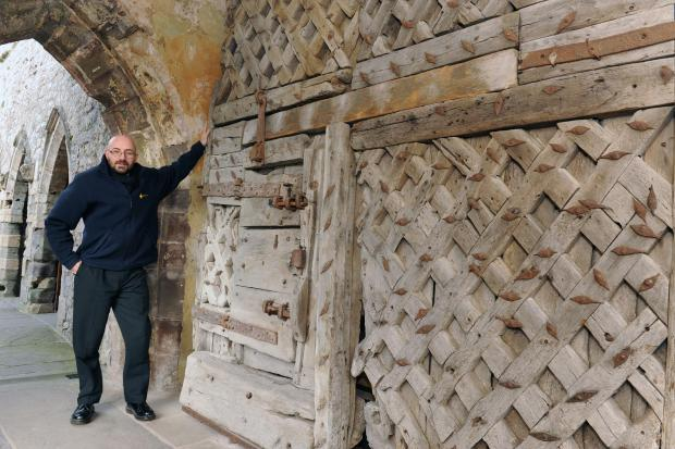 South Wales Argus: John Phillips with the oridinal catle door at Chepstow Castle. (2863240)