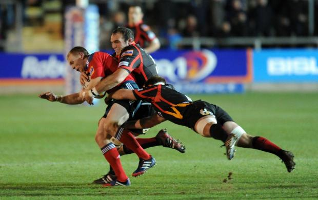 South Wales Argus: SKIPPER: Dragons lock Robert Sidoli, seen here tackling Keith Earls with Nic Cudd, takes over the captain's duties against the Blues in the absence of the injured Andrew Coombs