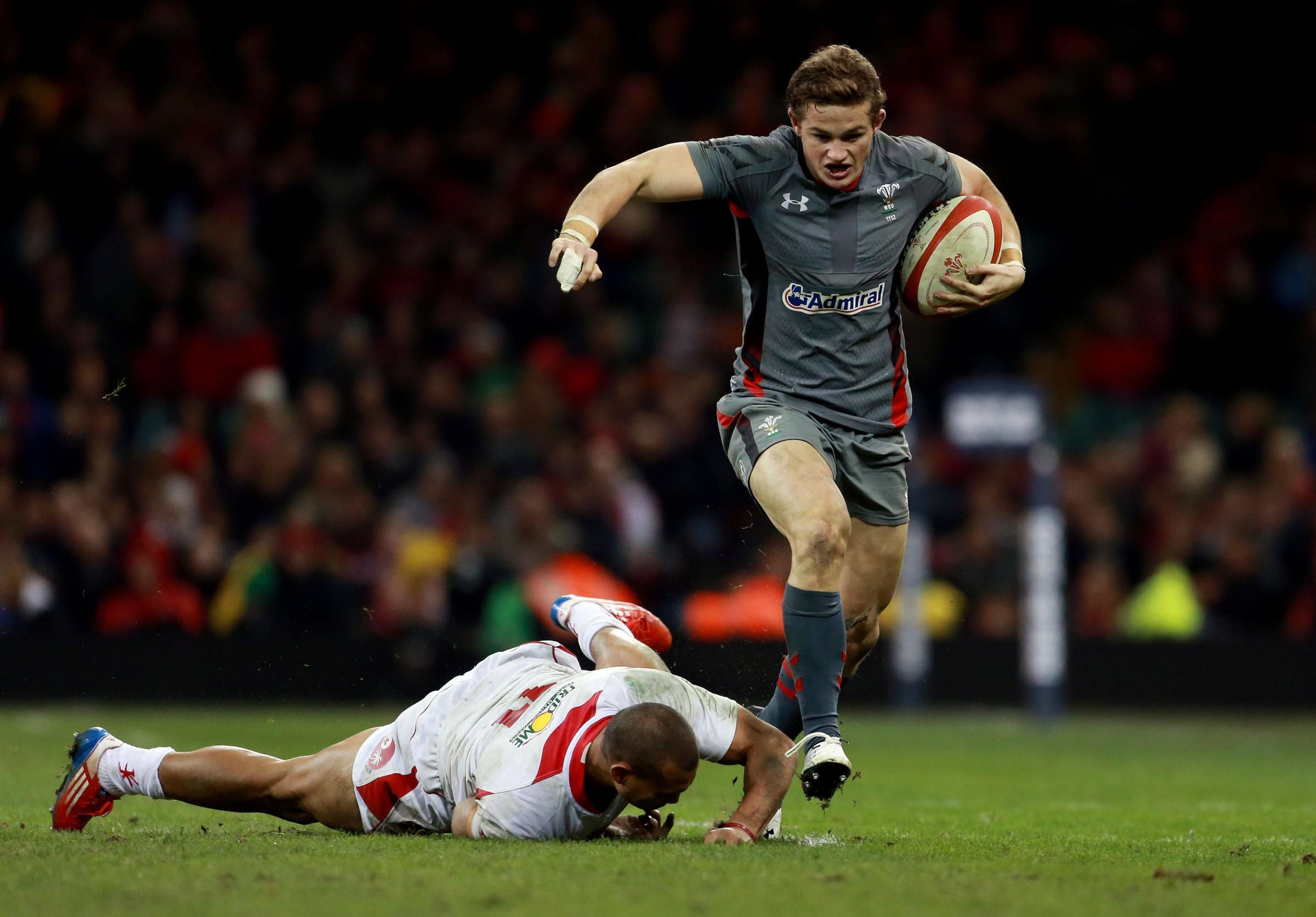 Wales Hallam Amos evades the tackle of Tonga's Will Helu during the Dove Men Series match at the Millennium Stadium, Cardiff. PRESS ASSOCIATION Photo. Picture date: Friday November 22, 2013. See PA Story RUGBYU Wales. Photo credit should read: David