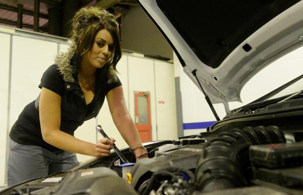 South Wales Argus: Ladies from Newport are being invited to a car maintenence workshop at Wessex Garages at Newport Retail Park this Thursday. Pictured is Natasha Liddle from Wessex Garages working under the bonnet.  (3560299)