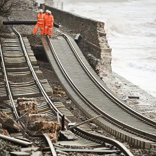 A huge length of railway track is exposed and left hanging after the sea wall collapsed in Dawlish, where high tides and strong winds have created havoc in the Devonshire town disrupting road and rail networks and damaging property.