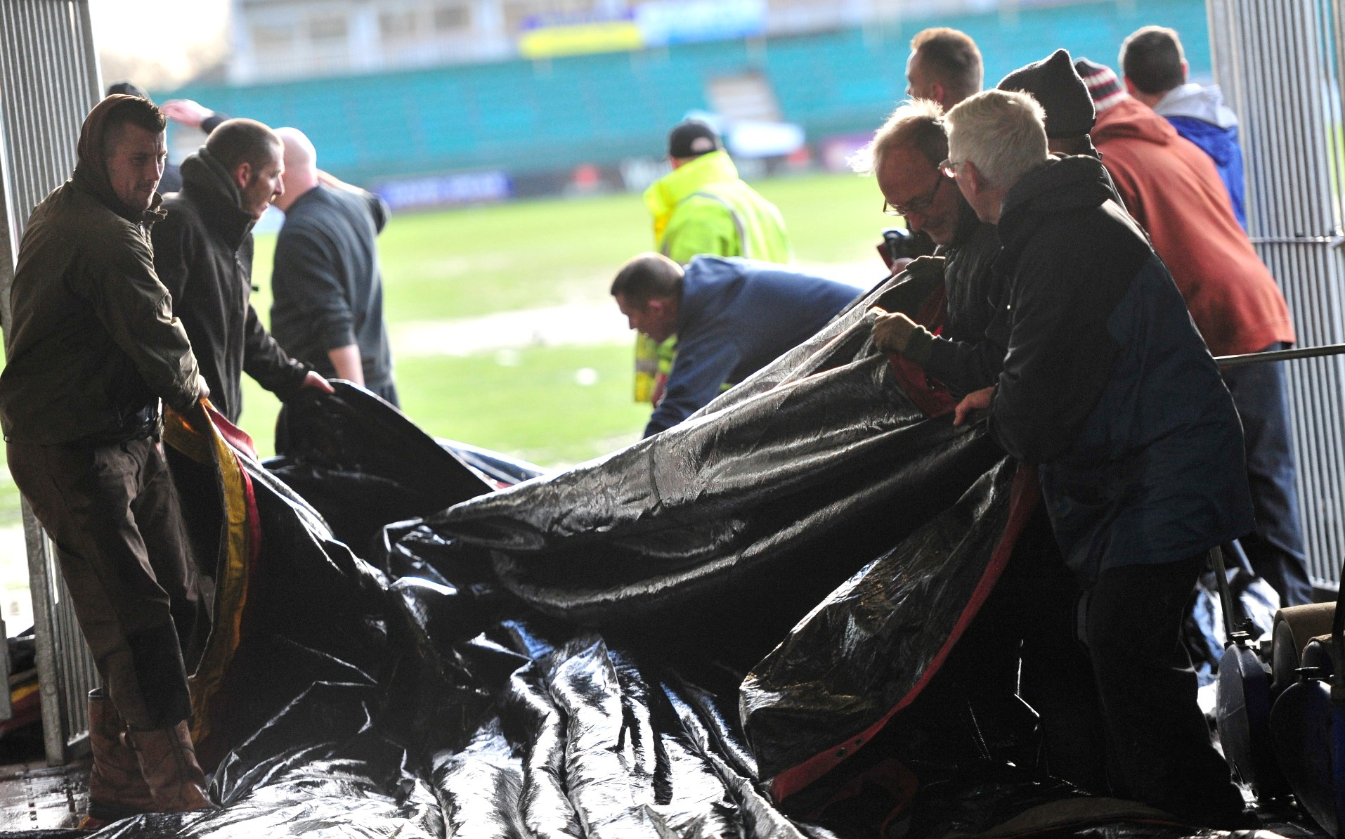 HARD WORK: Volunteers helped clear water off the covers on Rodney Parade this morning but to no avail