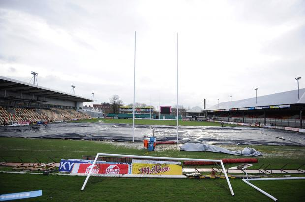 WATERLOGGED: The Rodney Parade pitch covered in an attempt to dry it out this morning