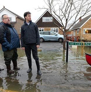 Ed Miliband has attacked David Cameron for giving up the fight against climate change and said the winter storms should serve as a