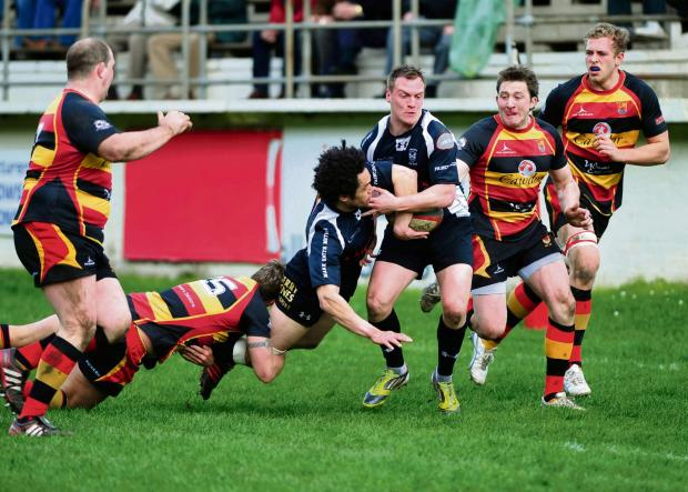South Wales Argus: Crosskeys' Leon Andrews hands off to Nathan Trowbridge as he is tackled. (838383)