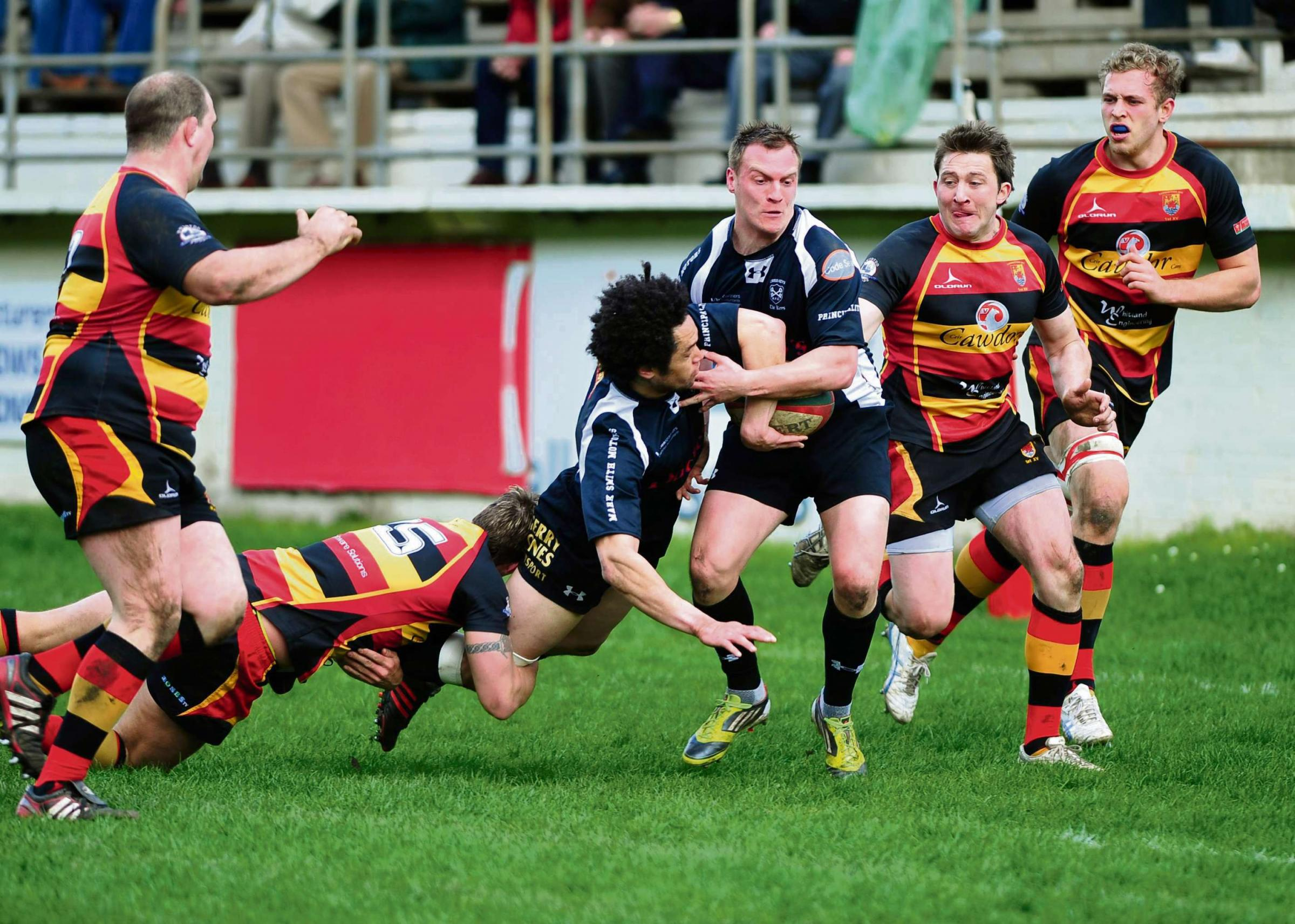 Crosskeys' Leon Andrews hands off to Nathan Trowbridge as he is tackled. (838383)