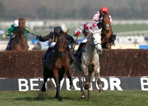 ON WAY TO VICTORY: Eventual winner O'Faolains Boy (centre left) ridden by Barry Geraghty competes with Smad Place ridden by Robert Thornton during the RSA Chase during Champion Day at Cheltenham yesterday