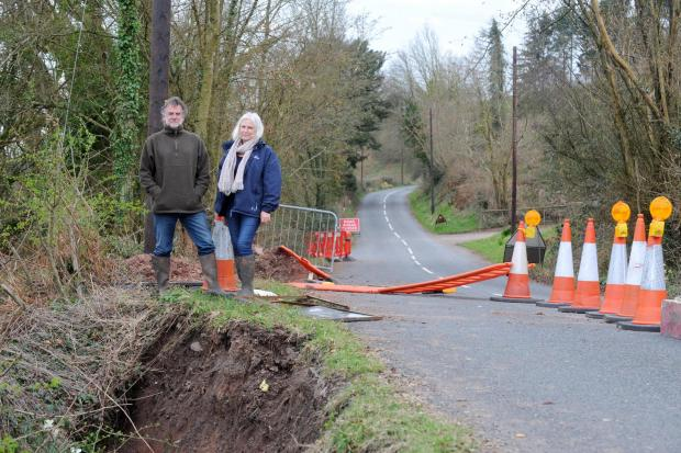 Tony and Lynne Jellard by one of the landslips near their home on the B4347 near Grosmont. The road has been shut for 2 months.