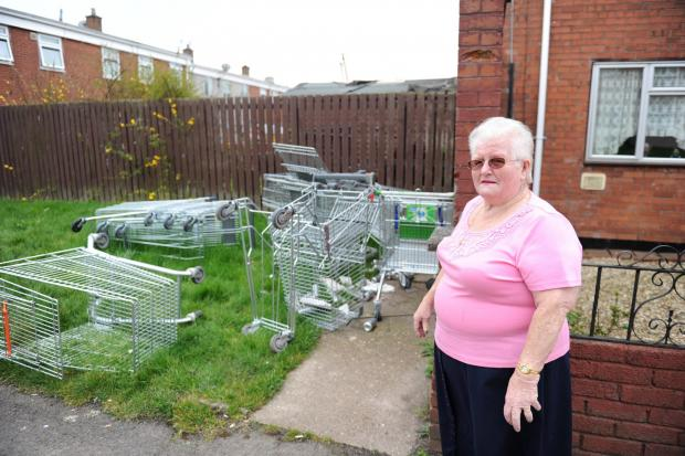 South Wales Argus: Cwmbran residents have complained to the council over fly-tipping in the area that includes 12 shopping trolleys.  Pictured is Mary Millar on Mead Lane with the large pile of shopping trolleys near her house. (5001424)
