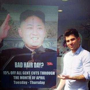 Barber Karim Nabbach standing next to a poster poking fun at North Korean leader Kim Jong-un unusual hairstyle, as North Korean officials visited the salon over the display of their leader's poster in the salon's window.
