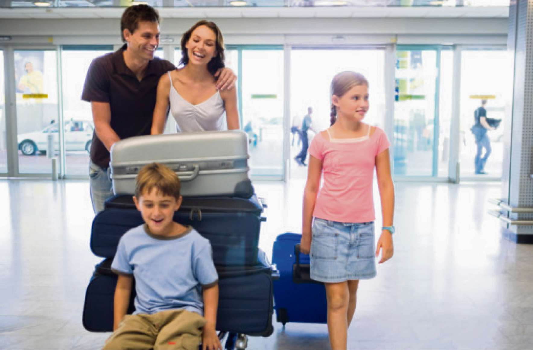 Family with cart of luggage in airport (6052272)