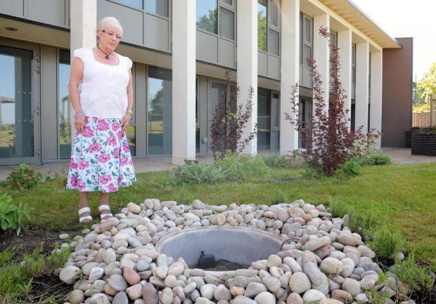 South Wales Argus: Jackie Lewis with the vandalised water feature at St David's Hospice in Newport. She donated the scupture after her son Steven, who was looked after by the hospice, died of stomach cancer. (6300791)