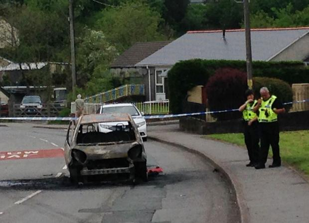 South Wales Argus: The burnt-out car and officers at the scene of the incident on Ystrad Deri in Tredegar. Pic Jen Mills.