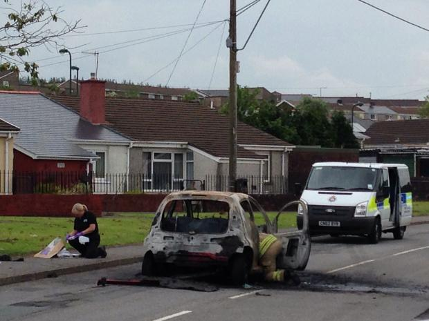 The burnt-out car and officers at the scene of the incident on Ystrad Deri in Tredegar. Pic Jen Mills.