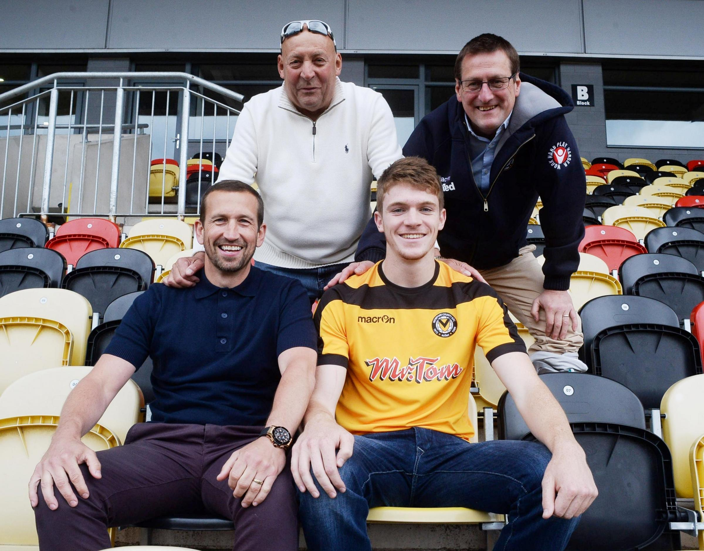 Newport County AFC new signing Kevin Feely, (ok), is welcomed to the stadium by manager Justin Edingburgh, (seated), and club chairman, Les Scadding, (top left) and Howard Greenhaf, director (6693247)