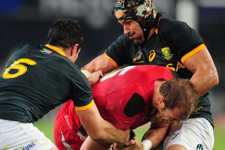 Wales' Alun-Wyn Jones, center, is tackled by South Africa's Francois Louw, left, and Victor Matfield, right, during their Rugby test match in Durban, South Africa, Saturday, June 14, 2014. (AP Photo). (7154912)