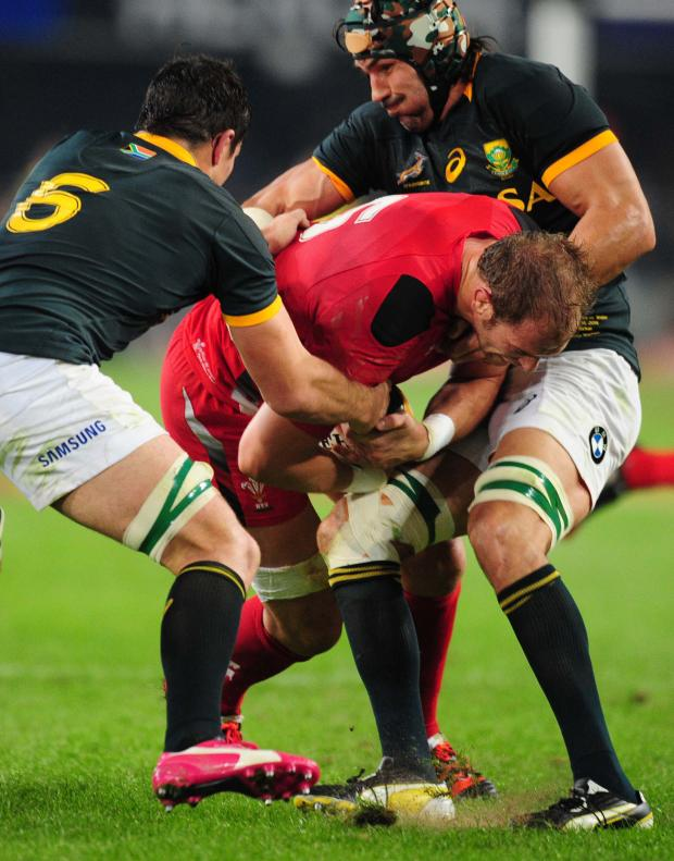 South Wales Argus: Wales' Alun-Wyn Jones, center, is tackled by South Africa's Francois Louw, left, and Victor Matfield, right, during their Rugby test match in Durban, South Africa, Saturday, June 14, 2014. (AP Photo). (7154912)