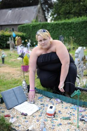 Catherine Board at her baby son Brandon's grave. She has handed a petition in to Torfaen council against new grave decoration policies.