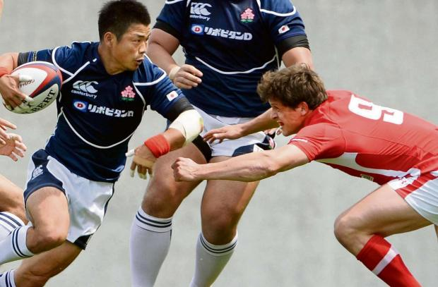 Wale's Lloyd Williams, right, tackles Japan's Fumiaki Tanaka during a rugby test in Osaka, western Japan, Saturday, June 8, 2013.   Welsh team defeated Japan 22-18. (AP Photo/Kyodo News) JAPAN OUT, MANDATORY CREDIT  (7522494)