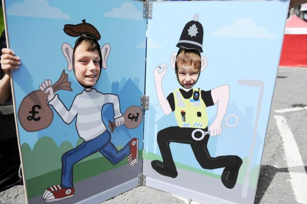 South Wales Argus: Blackwood Beach Party was held in the High Street which contained children's funfair rides, food and craft stalls.  Pictured playing cops and robbers are brothers Aaron 11 and Iaon Richardson 4 from Britannia. (7645610)