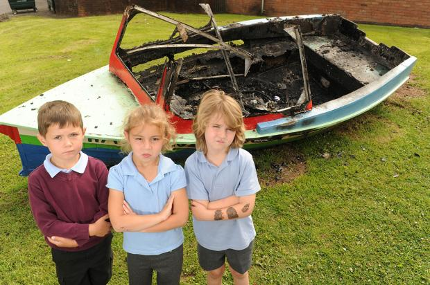 UPSET: Malpas Court  Primary School pupils, from left, James Rice, Aimee Saunders and  Gabriel Seager-Davies with the torched boat in their playground
