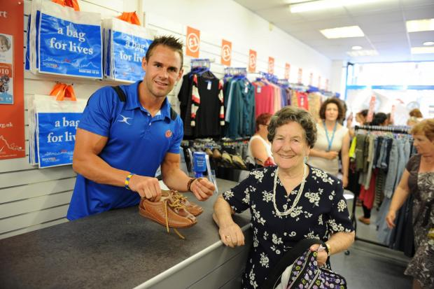 Welsh International and Newport Gwent Dragons player Lee Byrne opens a new Tenovus bargain £1 charity shop on the High Street in Newport.  Pictured serving the first customer is Lee with Thelma Lloyd from Newport. (8599015)