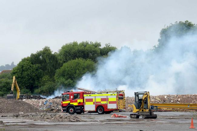STILL BURNING: Firefighters at the scene of the 100-tonne wood fire in the Lliswerry area of Newport