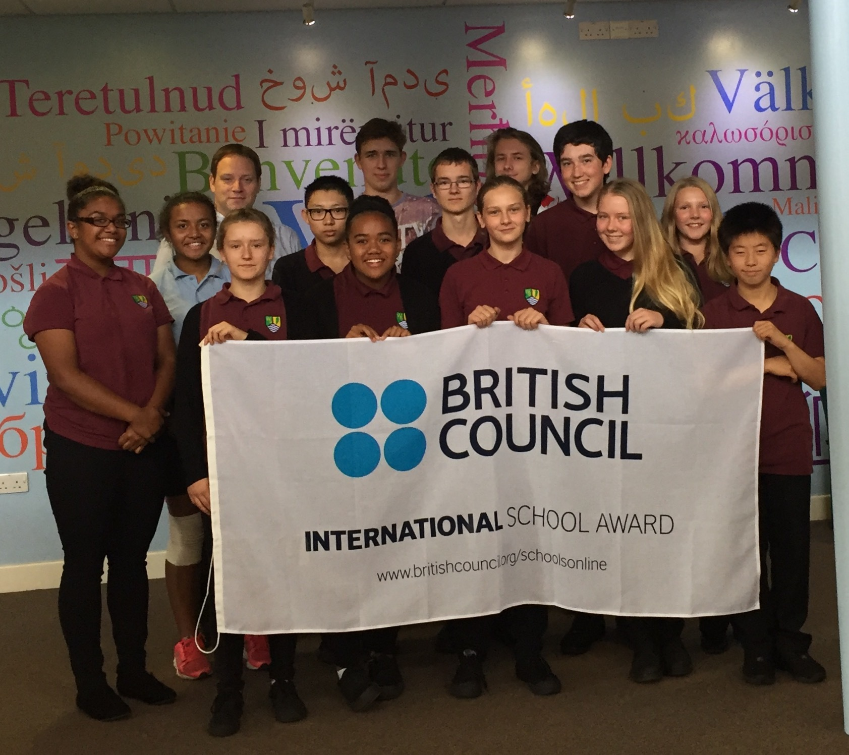 WINNERS: Head teacher of the school Rob Ford pictured with students and the British Council International School Award Flag