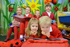 Tommy Burke, (front right) a Year 1 pupil helping nursery pupil Alys-Marie Hawkins-Price (left) with her reading in the nursery reading group