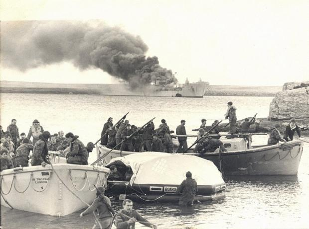 South Wales Argus: DISASTER: Survivors from the Sir Galahad make their way ashore as the stricken ship blazes
