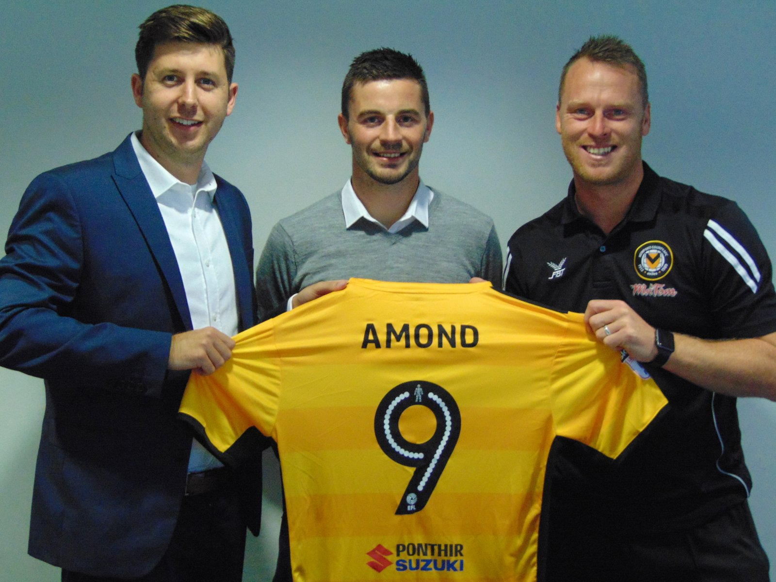 SIGNED: Padraig Amond, centre, with Exiles chief executive Alex Tunbridge, left, and manager Michael Flynn, right. Picture: Newport County AFC