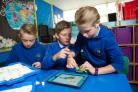 (L-R) Isaac Willmore, Callum David Williams and Callie Jones coding with Lego to make a robot