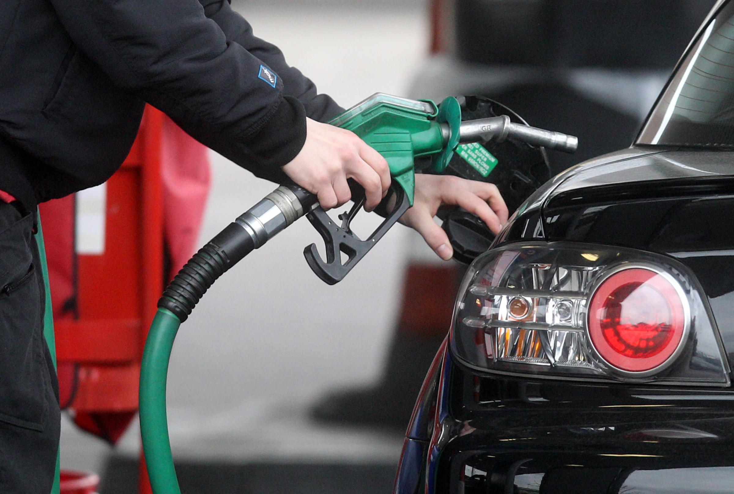 A person using  a petrol pump