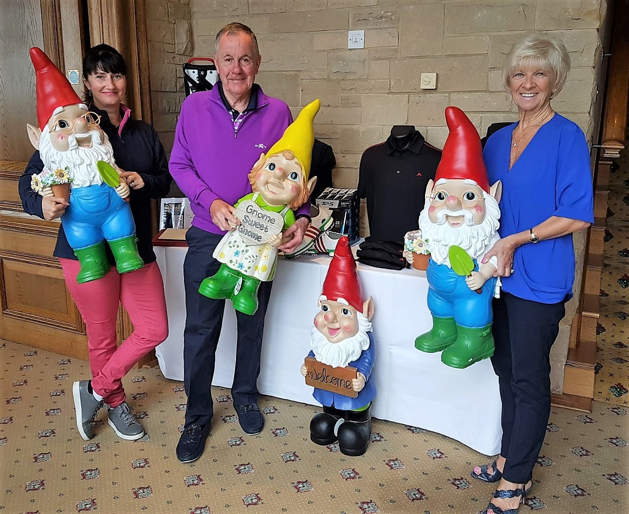 Golf gnomes: Roger Gambarini (centre), Julie  Huxtable on the left and Julie, Roger's wife on the right ( Hux and Gambo) with the unique Hospice Gnomes that are always presented to the team in 13th place