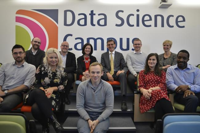 The eight ONA data analyst graduates with Eluned Morgan AM, Minister for Welsh Language and Lifelong Learning and UK National Statistician, John Pullinger