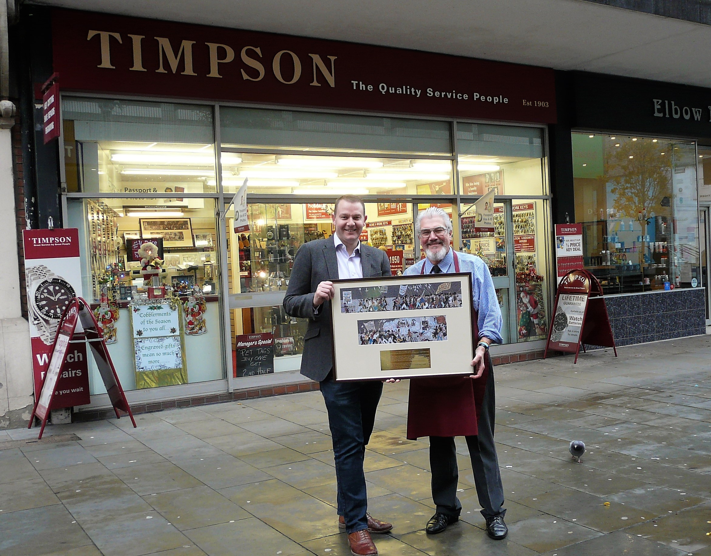 Cobbler Kelvin Reddicliffe (right) with Kris Broome, of St David's Hospice Care, at Timpson's, Austin Friars, Newport. Picture: DBPR