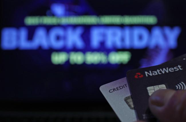 A person holding bank cards in front of a screen during 'Black Friday', in London. PRESS ASSOCIATION Photo. Picture date: Friday November 23, 2018. Photo credit should read: Yui Mok/PA Wire.