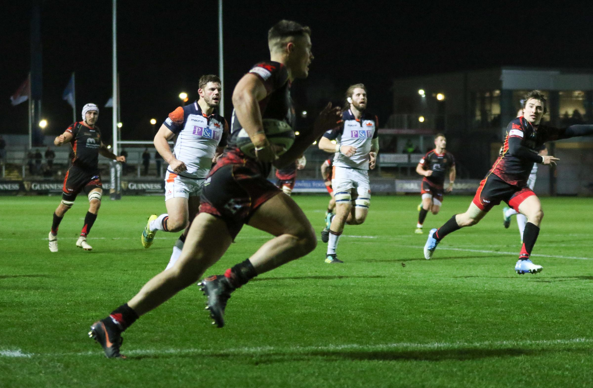 AT THE DOUBLE: Wing Jared Rosser runs over for the first of his two tries for the Dragons against Edinburgh