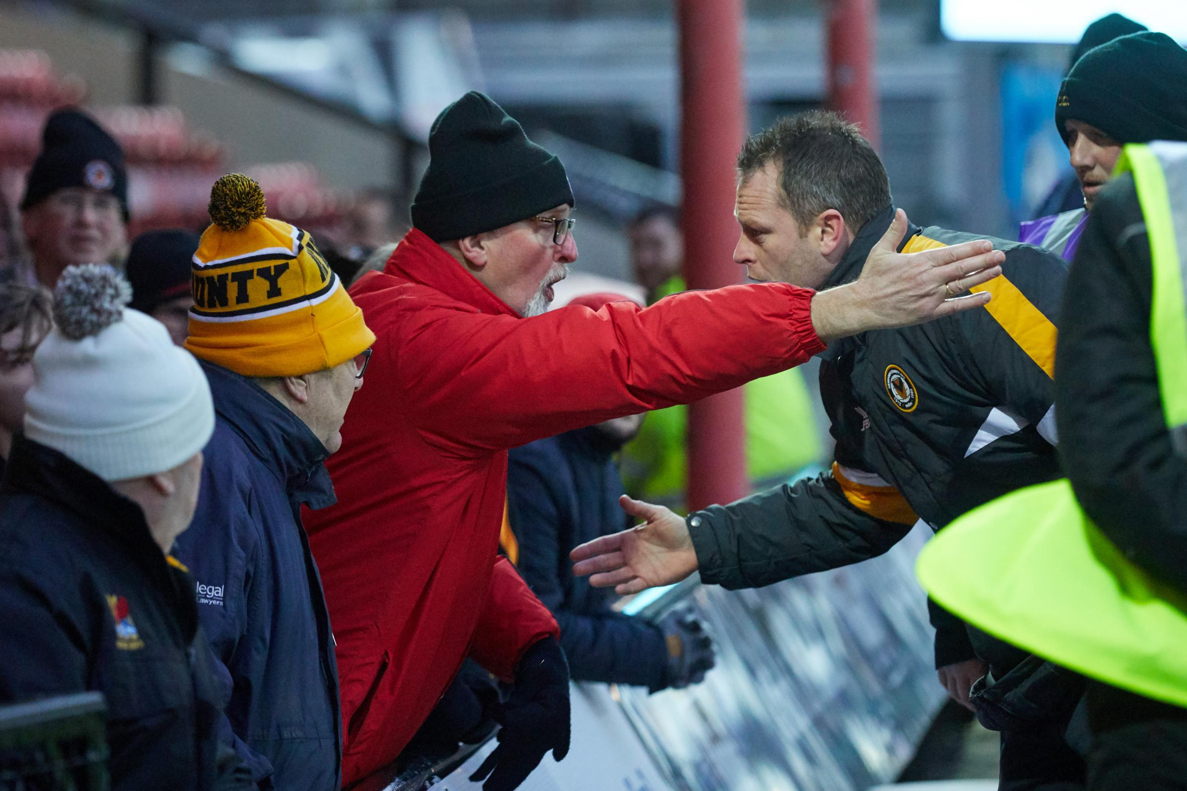 DISAGREEMENT: Newport County manager Michael Flynn, right, discusses his team selection with an angry fan after today's defeat at Grimsby Town. Pictures: Huw Evans Agency