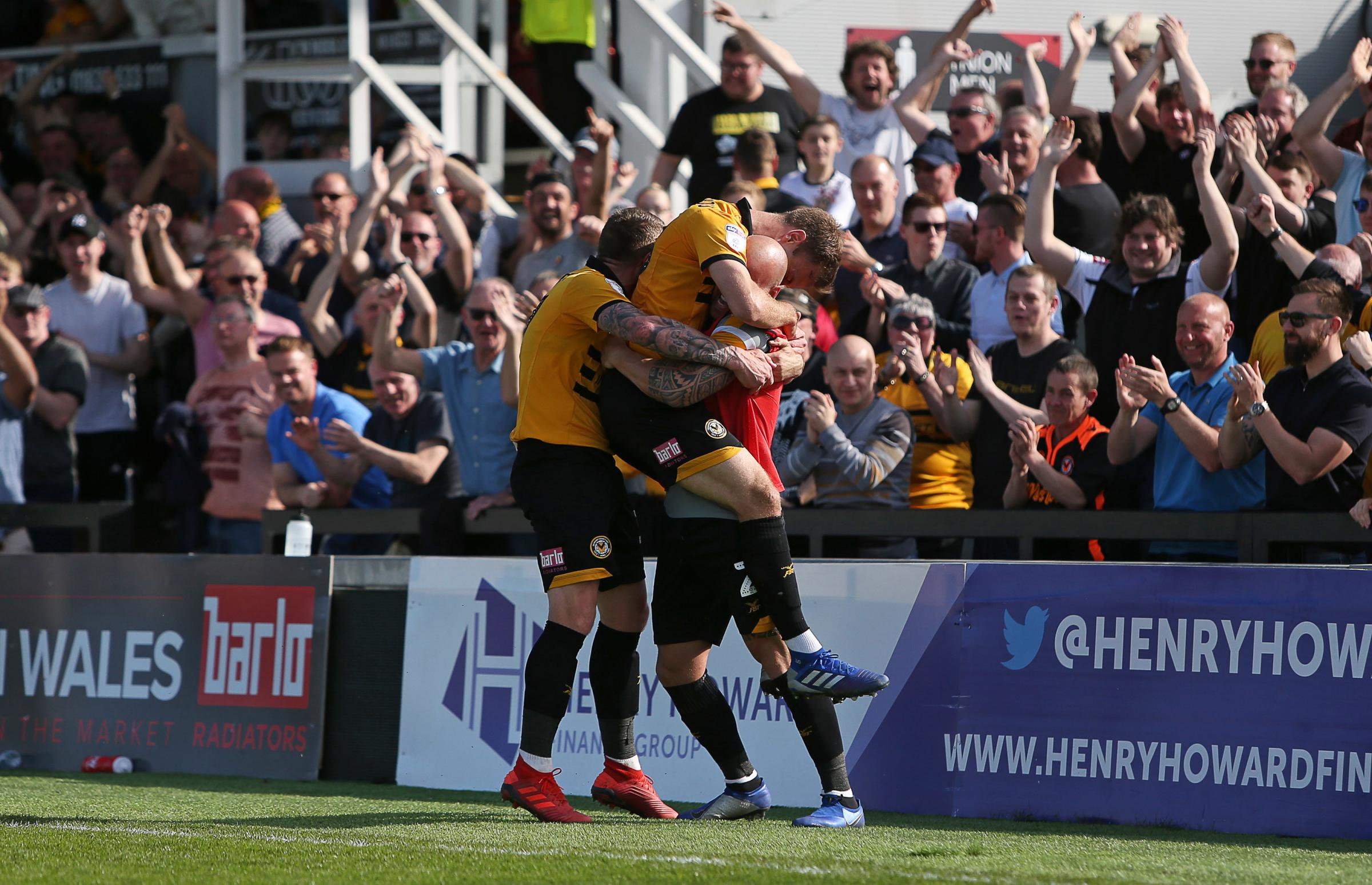 VICTORY: Mickey Demetriou celebrates his second goal with substitute David Pipe in front of the Newport County fans