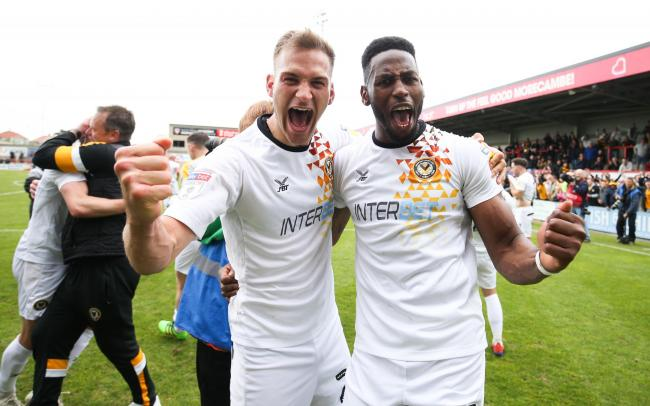 04.05.19 - Morecambe v Newport County, Sky Bet League 2 - Mickey Demetriou of Newport County and Jamille Matt of Newport County celebrate on hearing the news that Newport County had made the Division 2 Play Offs.