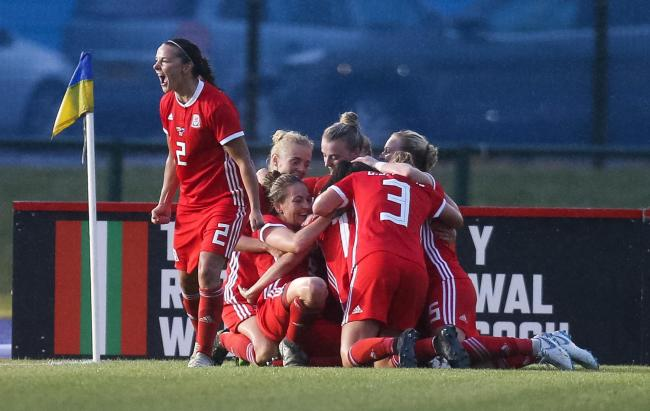 VICTORY: Wales' match-winner Kayleigh Green, centre, is mobbed by her teammates after netting the late winner against New Zealand